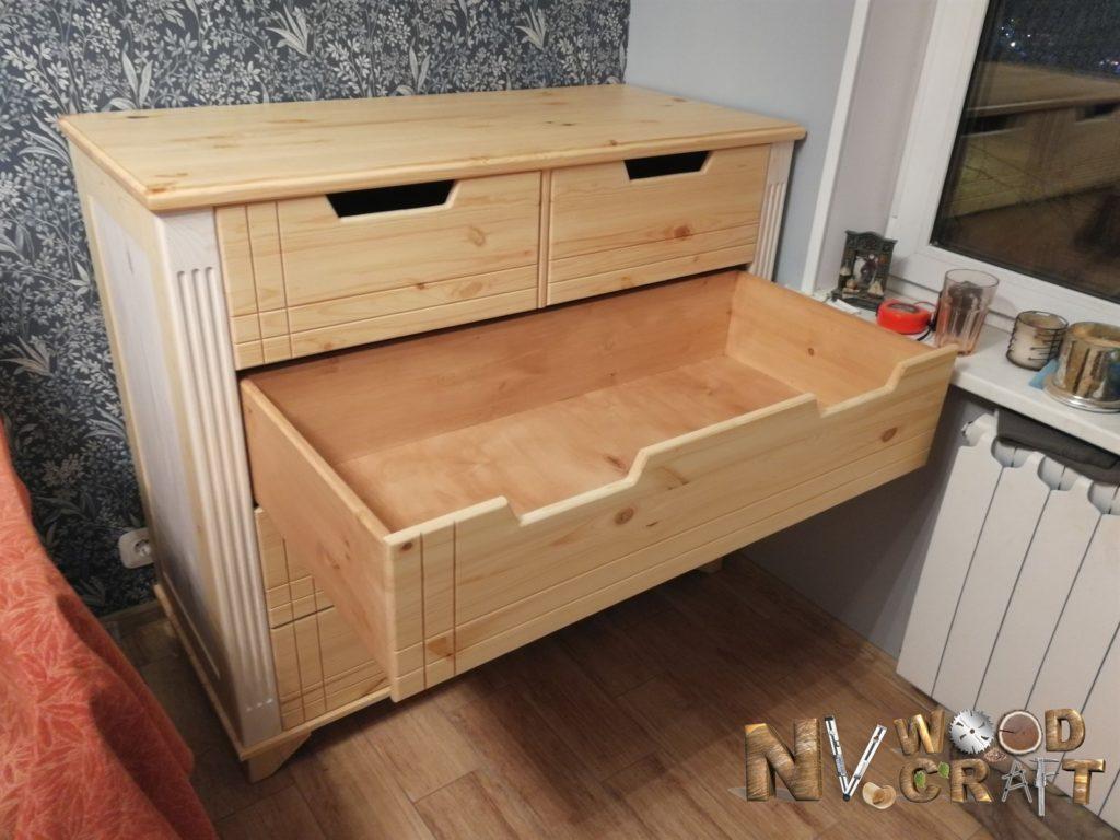 Выдвинутый большой ящика комода в спальню